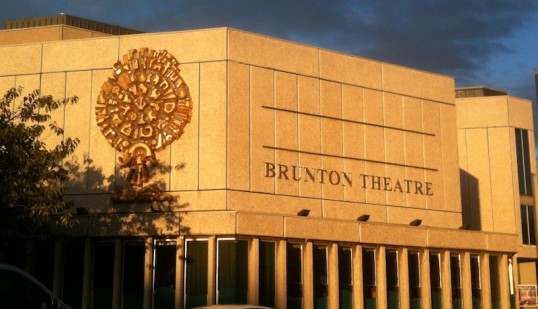 Picture of the Brunton Theatre's rather stark concrete facade, glowing in the evening sun.