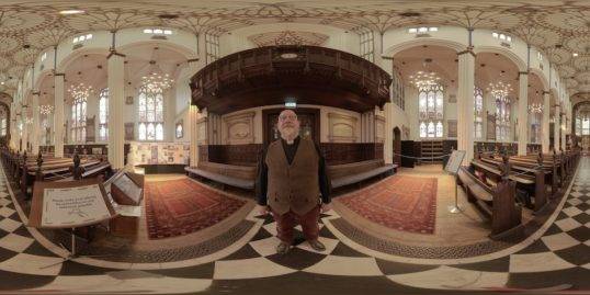 Markus Dünzkofer stands in the middle of St Johns Church, the church is ornate.